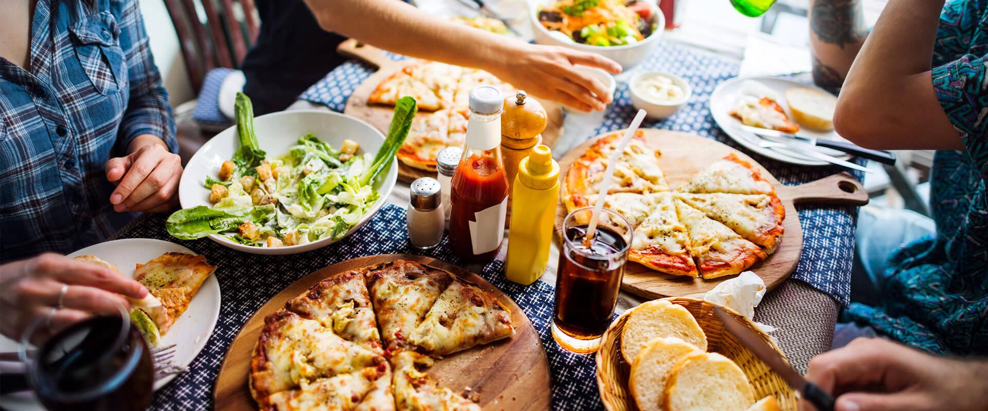 Varias personas comiendo pizza, pasta y pan italiano.