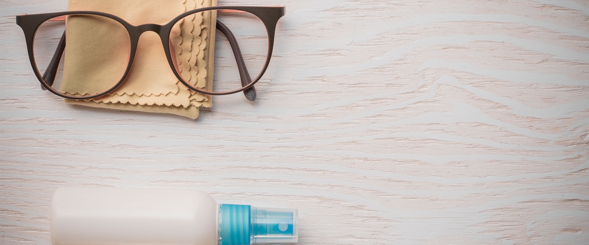 Imagen de lentes con su pañuelo y líquido limpiador.
