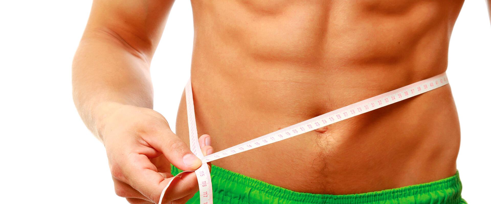 Hombre midiendo su cintura luego de usar el aparato de ejercicio Body Crunch Evolution.