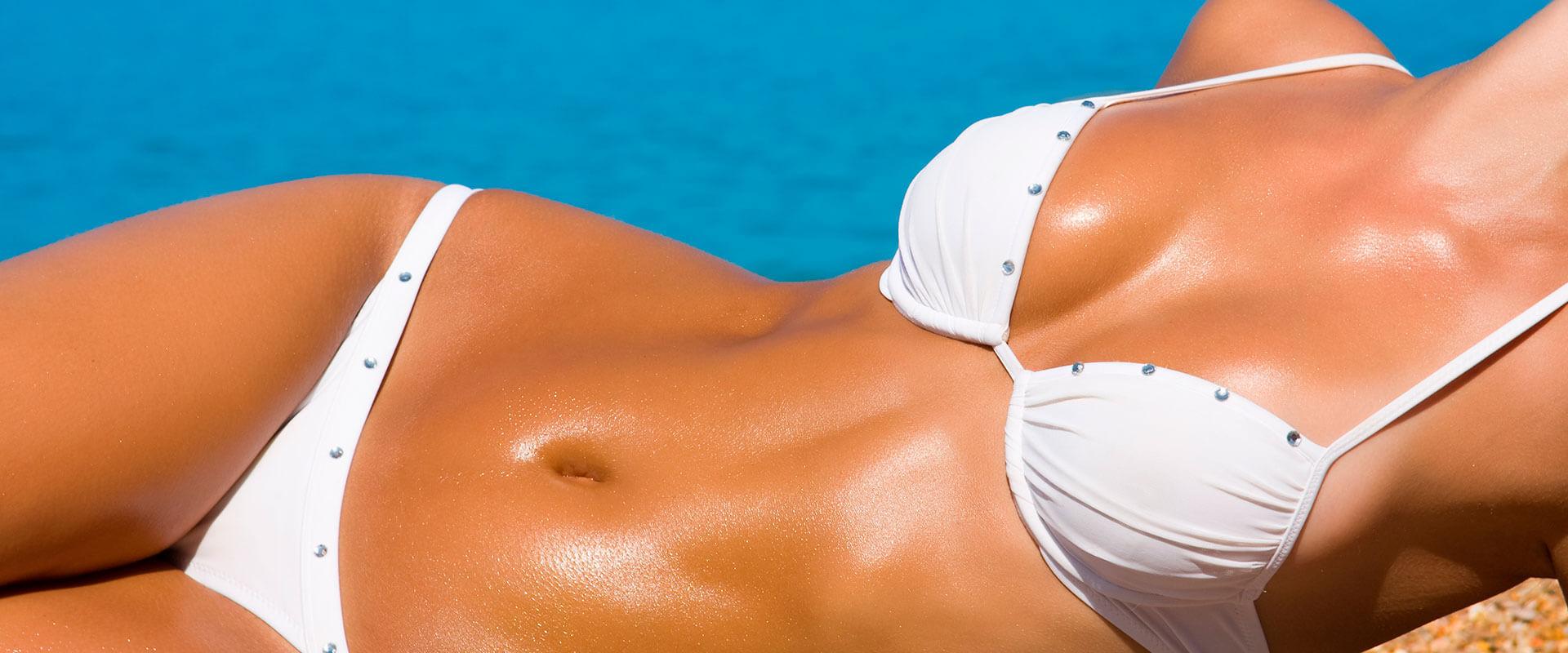 Mujer con abdomen plano, recostada en la playa gracias al uso de Gravity ABS, aparato de ejercicio.