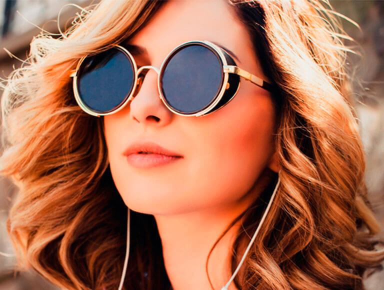 Mujer de cabello rizado, usando lentes circulares para el sol.