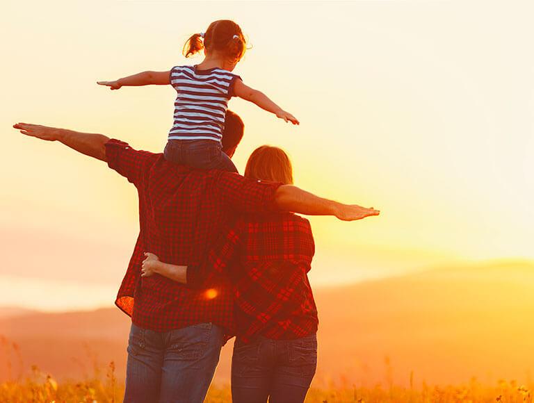 Familia de tres integrantes viendo el horizonte.