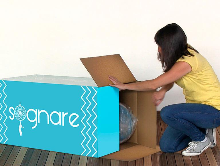 Mujer sacando el Colchón Sognare de su caja.