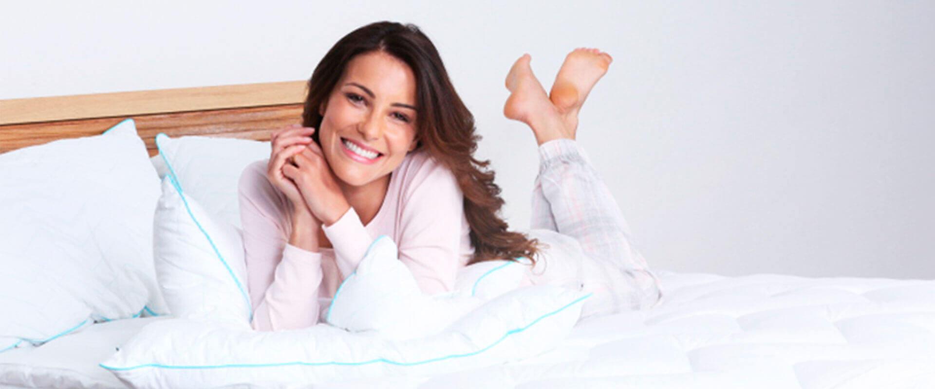 Mujer sonriente sobre su cama con colcha color blanco.